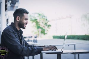 Cheerful men using laptop outdoors. Work, communication, study, freelance work, business concept